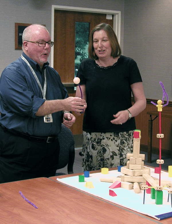(Courtesy of Chris Pfeiffer) Paul Burrows, left, and Paula Millington create a visual model that represents the strategic topic or theme their team was developing.