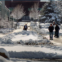 People walk on a snowy University of Utah campus.